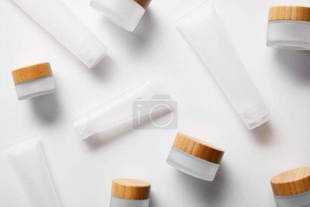 Photo pour Bocaux et tubes à crème dispersés pour produits cosmétiques sur fond blanc - image libre de droit