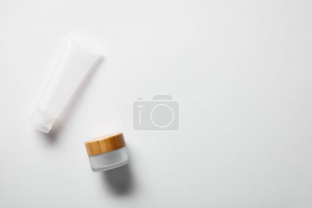 Photo pour Vue supérieure du tube de crème et du pot sur le blanc - image libre de droit