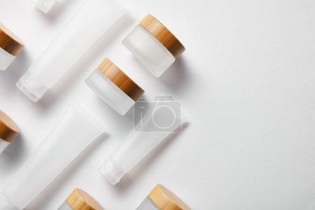 Photo pour Plat lay de tubes à crème et bocaux avec des chapeaux en bois sur blanc - image libre de droit