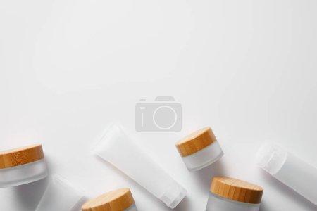 Photo pour Vue du haut de quelques pots vides et tubes de crème sur le blanc - image libre de droit