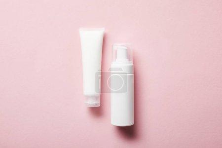 Photo pour Vue supérieure du tube de crème avec la crème de main et distributeur cosmétique sur le rose - image libre de droit