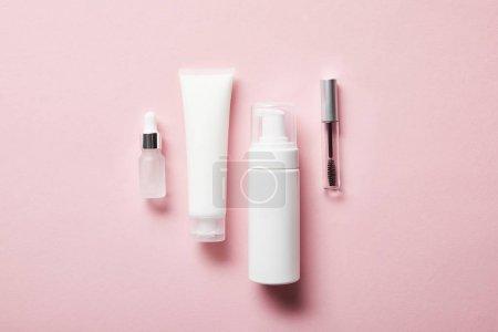 Photo pour Tube à crème avec crème pour les mains, distributeur cosmétique, pot vide et bouteille de mascara sur rose - image libre de droit