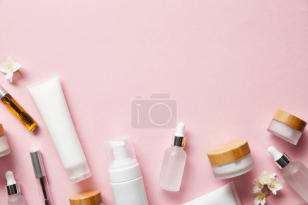 top view of cream tubes, cosmetic dispenser, empty jars and with hand cream, mascara bottles on pink