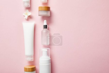 flat lay of different cosmetic containers and jasmine flower on pink