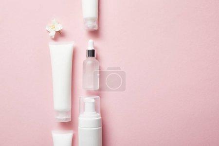 Photo pour Plat lay de bouteille en verre cosmétique, tubes à crème avec crème, distributeur cosmétique et fleur de jasmin sur rose - image libre de droit