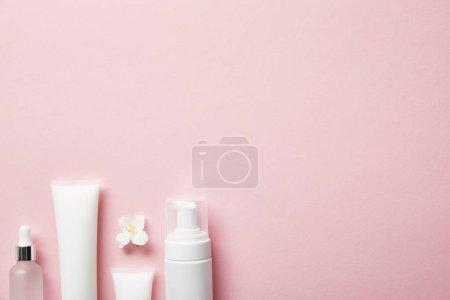 Photo pour Vue supérieure de la bouteille en verre cosmétique vide, tubes de crème avec la crème, distributeur cosmétique et fleur de jasmin sur le rose - image libre de droit