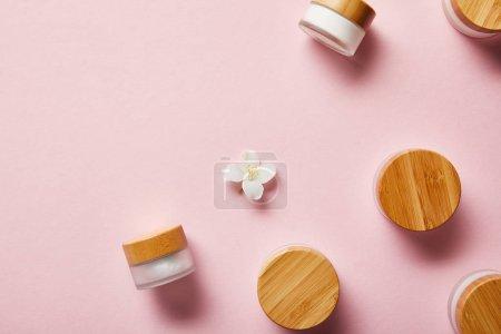 Photo pour Vue du haut des bocaux dispersés avec la crème et les chapeaux en bois, et la fleur de jasmin au milieu sur le rose - image libre de droit