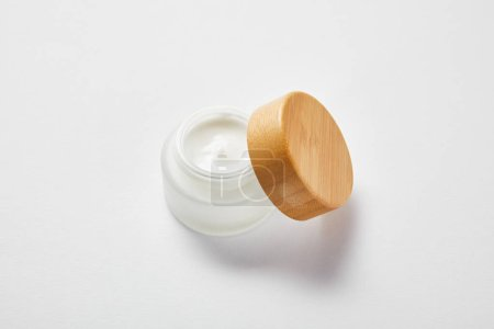 Photo for Open glass jar with cream and wooden cap on white - Royalty Free Image
