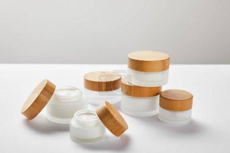 Photo pour Beaucoup de pots en verre avec des bouchons en bois sur blanc - image libre de droit