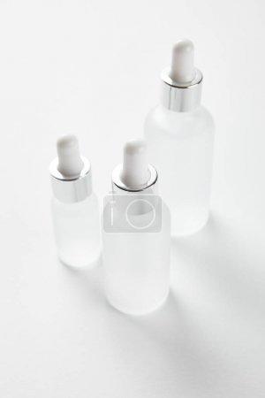 Photo pour Trois bouteilles en verre avec sérum sur blanc - image libre de droit