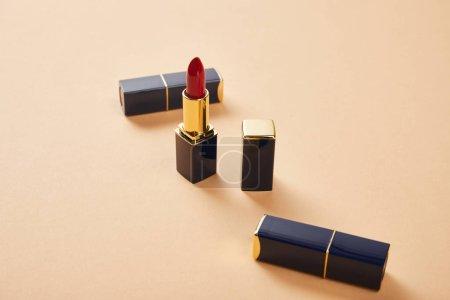 Photo pour Plan rapproché de divers rouge à lèvres dans des tubes sur le beige - image libre de droit