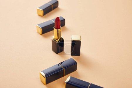 Photo pour Gros plan de divers rouges à lèvres dans des tubes sur beige - image libre de droit