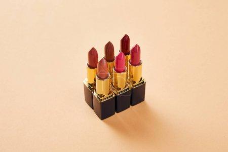 Foto de Varios tonos rojos de los labiales en beige - Imagen libre de derechos