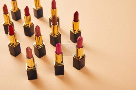Photo pour Différentes nuances rouges de rouges à lèvres sur beige avec espace de copie - image libre de droit