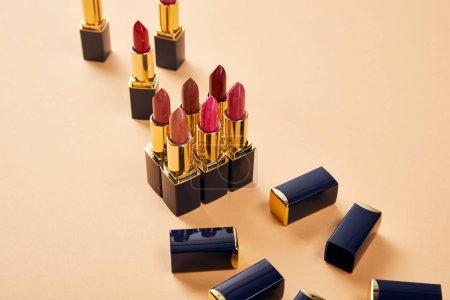 Photo pour Différentes nuances de rouges à lèvres sur beige - image libre de droit