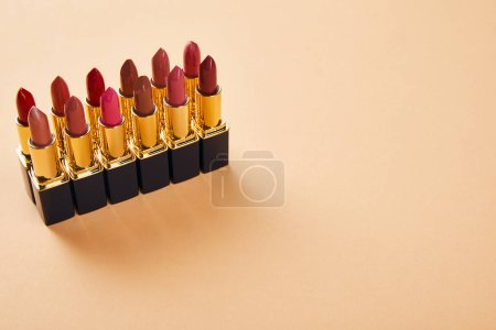 Photo for Various shades of lipsticks on beige with copy space - Royalty Free Image