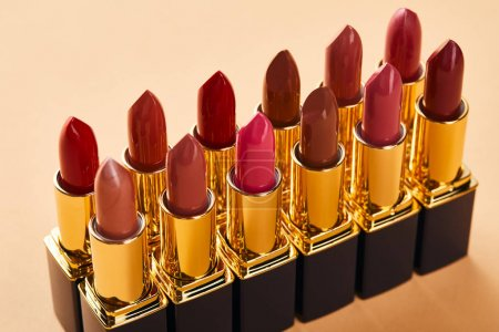 Photo for Close up of red shades of lipstick in tubes on beige - Royalty Free Image
