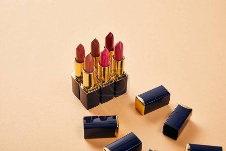 Photo pour Différentes nuances rouges de rouge à lèvres en tubes sur beige - image libre de droit