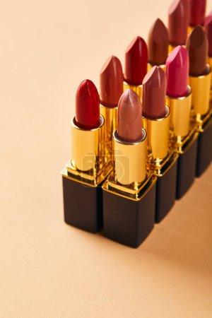 Photo pour Plan rapproché des nuances de rouge à lèvres dans des tubes sur le beige - image libre de droit