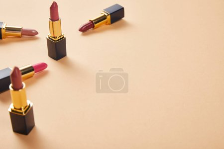 Photo for Various shades of lipstick in tubes on beige with copy space - Royalty Free Image