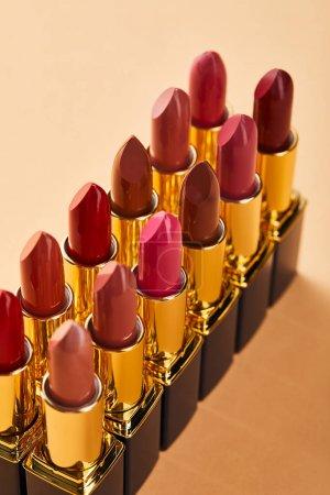 Photo pour Différentes nuances rouges de rouge à lèvres dans des tubes sur beige - image libre de droit