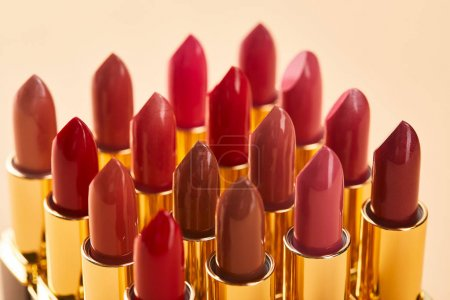 Photo pour Gros plan de différentes nuances rouges de rouge à lèvres dans des tubes isolés sur beige - image libre de droit