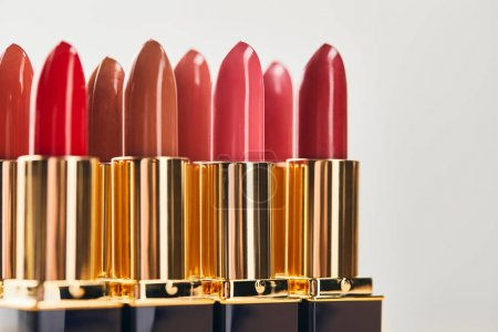 Photo pour Selective focus of various red shades of lipsticks isolated on grey - image libre de droit