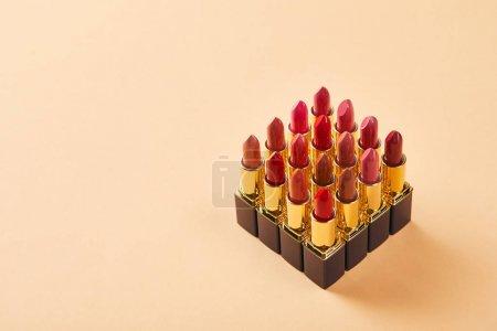 Photo pour Différents rouges à lèvres sur beige avec espace de copie - image libre de droit