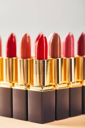 Photo for Various red lipsticks on beige and grey - Royalty Free Image