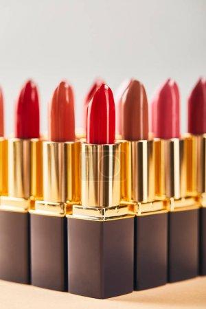 Photo pour Différents rouges à lèvres rouges sur beige et gris - image libre de droit
