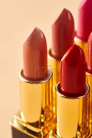 Photo pour Gros plan de diverses nuances rouges de rouge à lèvres dans des tubes sur beige - image libre de droit