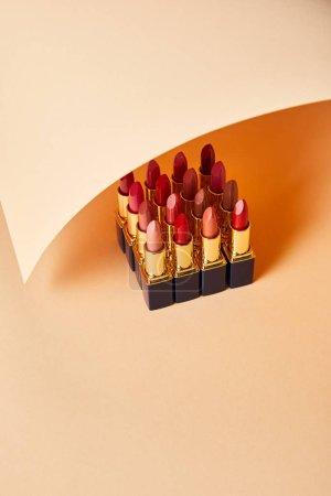 Photo pour Différentes nuances rouges de rouges à lèvres sur beige - image libre de droit