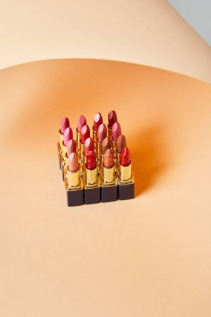 Foto de Diferentes tonos rojos de lápices labiales en beige - Imagen libre de derechos