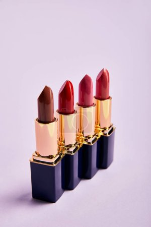 Photo for Various red lipsticks in tubes on violet - Royalty Free Image