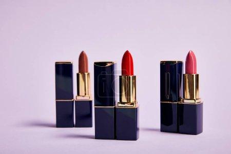 Foto de Various red shades of lipsticks in tubes on violet - Imagen libre de derechos
