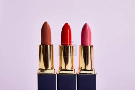 Foto de Varios tonos rojos de labiales aislados en violeta - Imagen libre de derechos