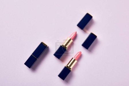 Photo pour Vue de dessus de différentes nuances roses de rouges à lèvres en tubes sur violet - image libre de droit