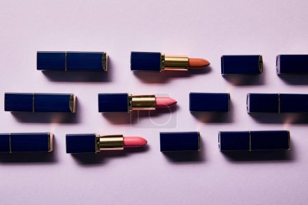 Foto de Flat lay with different pink shades of lipsticks in tubes on violet - Imagen libre de derechos