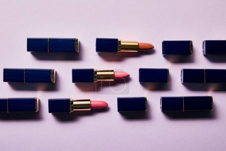 Photo for Flat lay with different pink shades of lipsticks in tubes on violet - Royalty Free Image