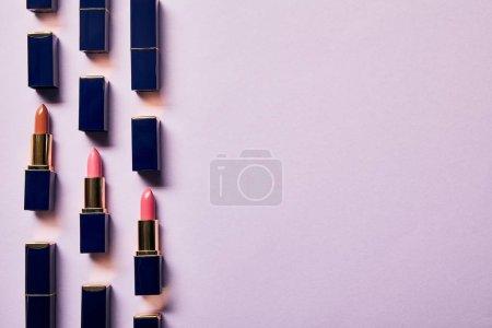 Photo pour Pose plate avec différentes nuances roses de rouges à lèvres sur violet avec espace de copie - image libre de droit
