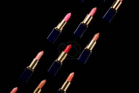 Photo pour Pose plate avec différentes nuances de rouges à lèvres dans des tubes isolés sur noir - image libre de droit