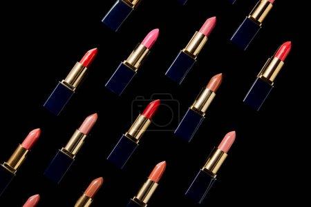 Photo pour Plat se sont couchés avec diverses nuances de rouges à lèvres isolés sur le noir - image libre de droit