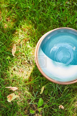 top view of blue empty ceramic bowl on green grass