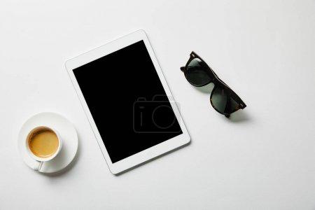 Foto de Vista superior de la tableta digital, café y vasos en la superficie blanca - Imagen libre de derechos