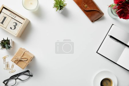 Photo for Top view of blocks with numbers and letters, notepad, pen, case, glasses, plants and candle on white surface - Royalty Free Image