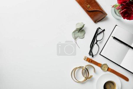 Foto de Vista superior de la joyería, bloc de notas, pluma, vasos, caja, plantas y café en la superficie blanca - Imagen libre de derechos