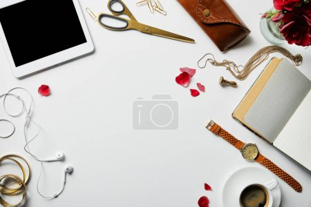 Foto de Top view of digital tablet, notepad, case, earphones, plants, office supplies and coffee with jewelry on white surface - Imagen libre de derechos