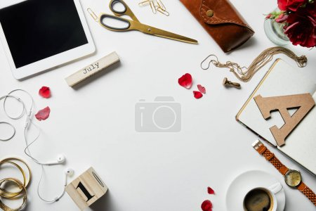 Photo for Top view of digital tablet, earphones, jewelry, case, flowers, office supplies and coffee on white surface - Royalty Free Image