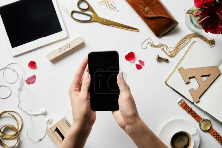 cropped view of woman holding smartphone in hands over digital tablet, earphones, jewelry, case, flowers, office supplies and coffee on white surface