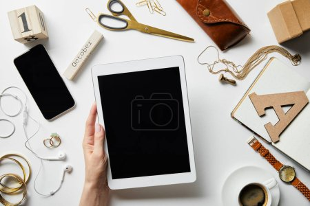 Foto de Vista recortada de la mujer sosteniendo la tableta digital cerca de teléfono inteligente, auriculares, joyas, estuche, flores, artículos de oficina y café en la superficie blanca - Imagen libre de derechos